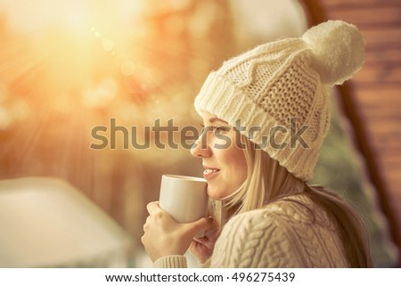 Female in white with cup of coffee at the winter weather under sunlight