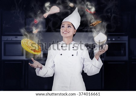 Female Indian chef juggling while cooking in the kitchen with magic and wearing cooking clothes - stock photo