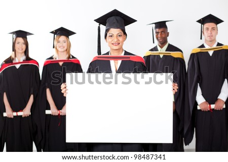 female indian graduate holding white board with classmates in background - stock photo