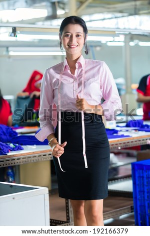 Female Indonesian tailor, dressmaker or designer standing proudly in an Asian textile factory, it is her workplace
