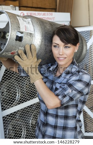 Female industrial worker carrying a propane cylinder - stock photo