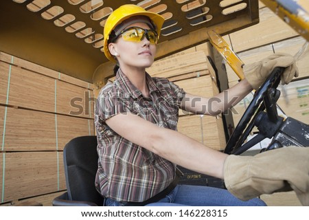 Female industrial worker driving forklift truck with stacked wooden planks in background - stock photo
