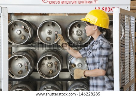 Female industrial worker taking out propane cylinder - stock photo