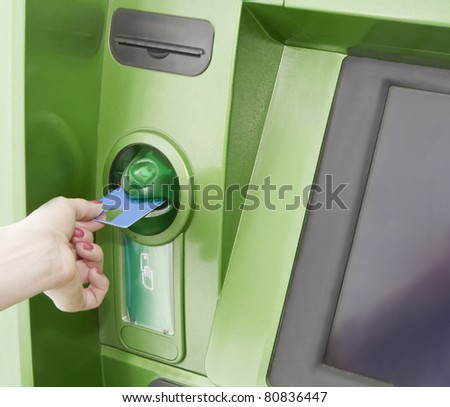Female inserts a plastic card in the ATM - stock photo