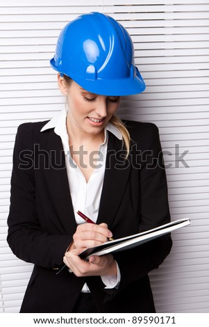 Female Inspector Checking Notes in a blue hard hat conceptual of architect, engineer, or construction. - stock photo