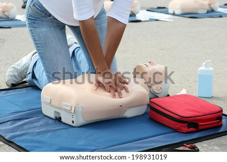 Female instructor showing CPR on training doll - stock photo