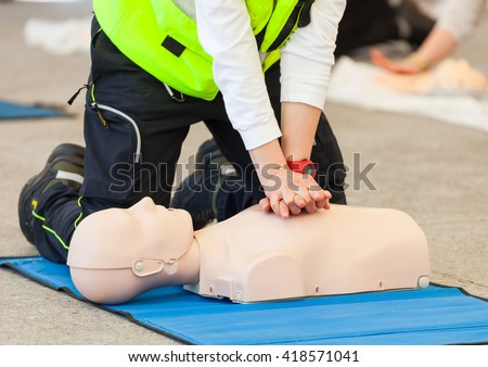 Female instructor showing CPR on training doll. - stock photo