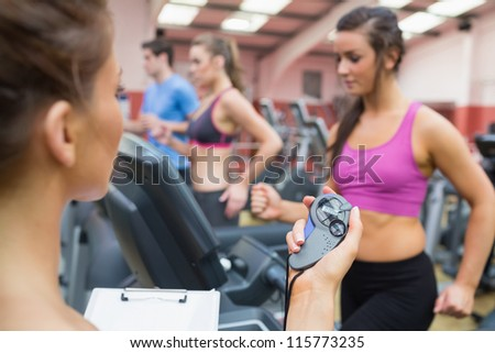 Female instructor using stopwatch in the gym - stock photo