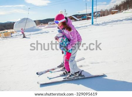 Female instructors teach a child skiing on winter resort - stock photo