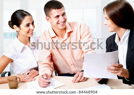 Female insurance agent is talking with a young couple - stock photo