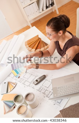 Female interior designer with color swatches and laptop at office - stock photo