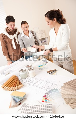 Female interior designer with two clients at office choosing colors - stock photo