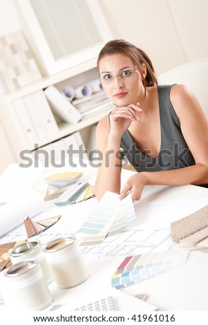 Female interior designer working at office with color swatch choosing color - stock photo