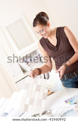 Female interior designer working at office with color swatch choosing color of tiles - stock photo