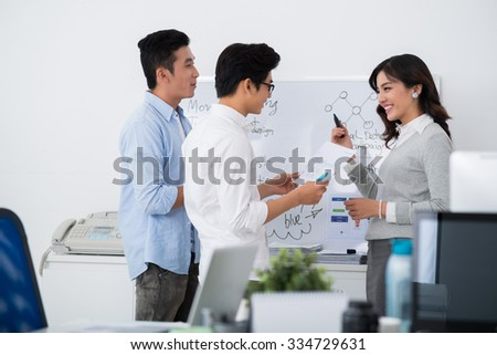 Female interpreter explaining business strategy to her colleagues - stock photo