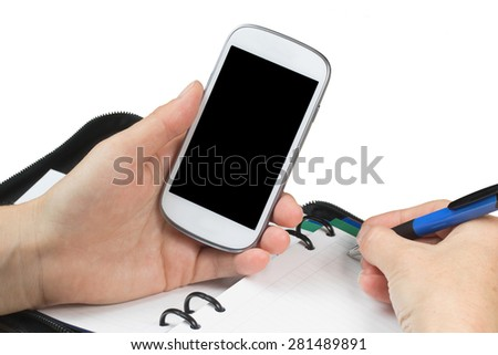 Female is holding a cell phone and writing in managerial organizer. All is isolated on the white background. All potential trademarks are removed.