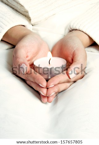 Female is holding lighted candle in hands - stock photo
