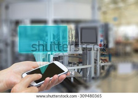 Female is using the smart phone Blank transparent rectangle radiates from the screen of smart phone. The automatic production line is in the background. The edges of the pictures are blurred. - stock photo