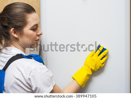 Female janitor cleaning refrigerator door with sponge - stock photo