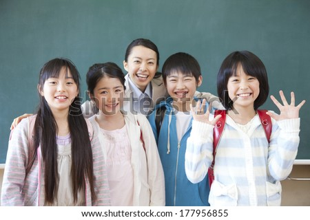 Female Japanese teacher and Primary Japanese boy and Japanese girl with a smile