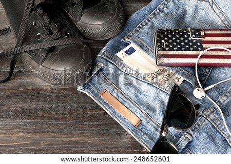 Female jeans with money in the pocket and some accessories lying on floor - stock photo
