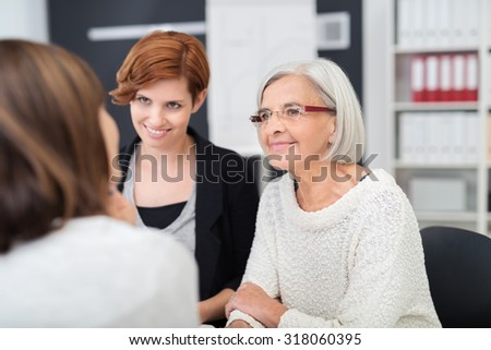 Female job applicant with two women personnel officers giving them a presentation on her qualifications as they listen attentively - stock photo