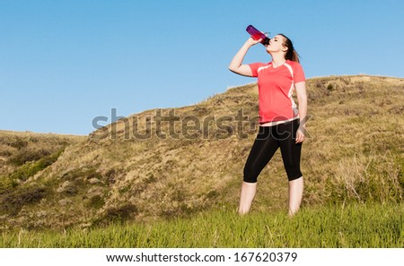 Female jogger drinking from a water bottle in the hills - stock photo