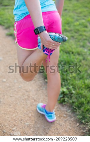 Female jogger jogging outside at the sunset - stretching of legs
