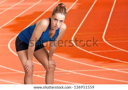Female jogger resting after a long run on a wet athletics running track - stock photo