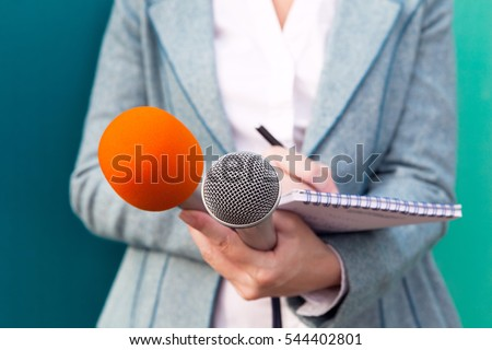 Female journalist at news conference, writing notes, holding microphones