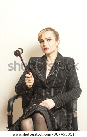 Female Judge With  Wooden Gavel In Chair - stock photo