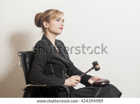 Female Judge With Wooden Gavel in office chair - stock photo