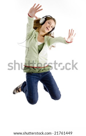 female jumping while listening to music against white background - stock photo