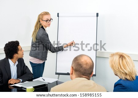 Female Junior Associate explaining diagram on filpchart to colleagues in conference room - stock photo