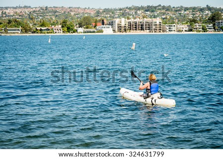 Female kayaking in the bay - stock photo