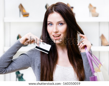Female keeps credit card in footwear shop with great variety of stylish shoes - stock photo