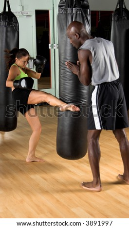 Female kick boxer kicking the heavy bag while her trainer watches - stock photo