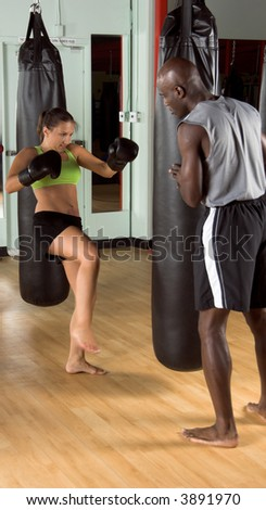 Female kick boxer launching a kick at the heavy bag while her trainer watches - stock photo
