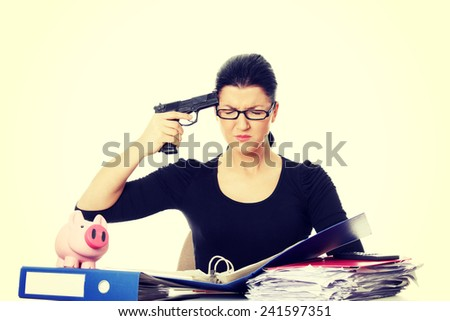 Female killing her self while filling out tax forms while sitting at her desk. - stock photo