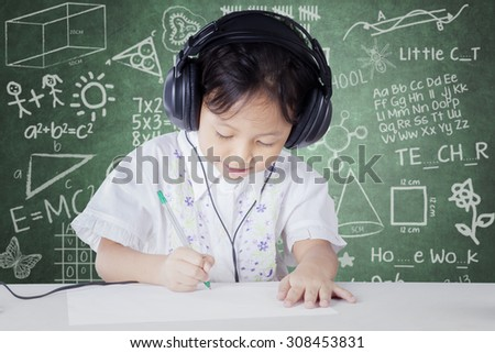 Female kindergarten school student studying in the classroom while wearing headphones and write on the paper - stock photo
