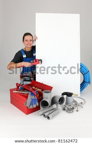 Female labourer surrounded by tools - stock photo