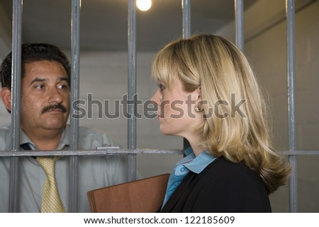 Female lawyer meeting with client in jail for discussion - stock photo
