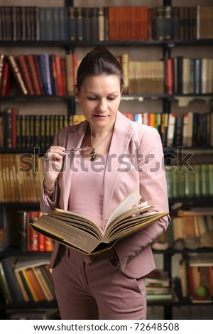 Female lawyer reading a thick law book while holding eyeglasses in her mouth