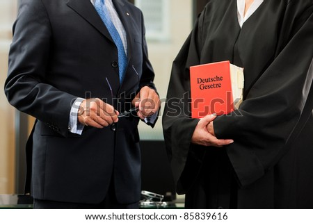 Female lawyer with civil law code and client - only torsos to be seen, close-up - stock photo