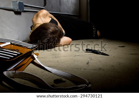 female laying dead on a street alley with a knife murder weapon.  the crime scene is a dark street alley. - stock photo