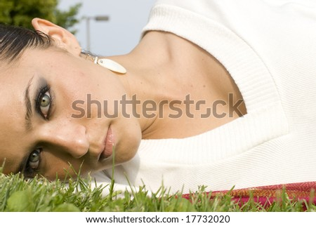 Female laying in the grass with a white top and earrings - stock photo