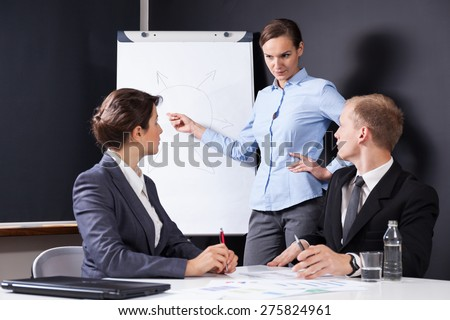 Female leader drawing chart on the board - stock photo