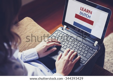 Female learning dutch at home with a laptop computer at home. - stock photo