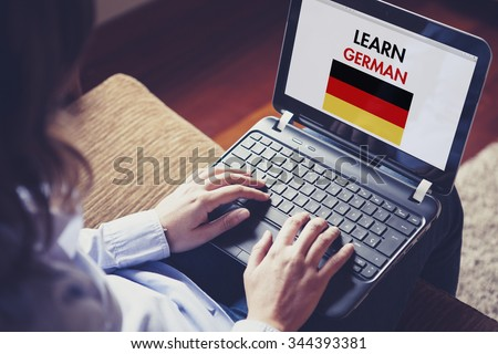 Female learning german at home with a laptop computer at home. - stock photo