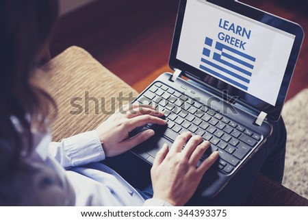 Female learning greek at home with a laptop computer at home. - stock photo